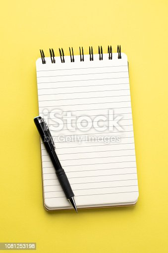 Spiral notebook and pencil on yellow background