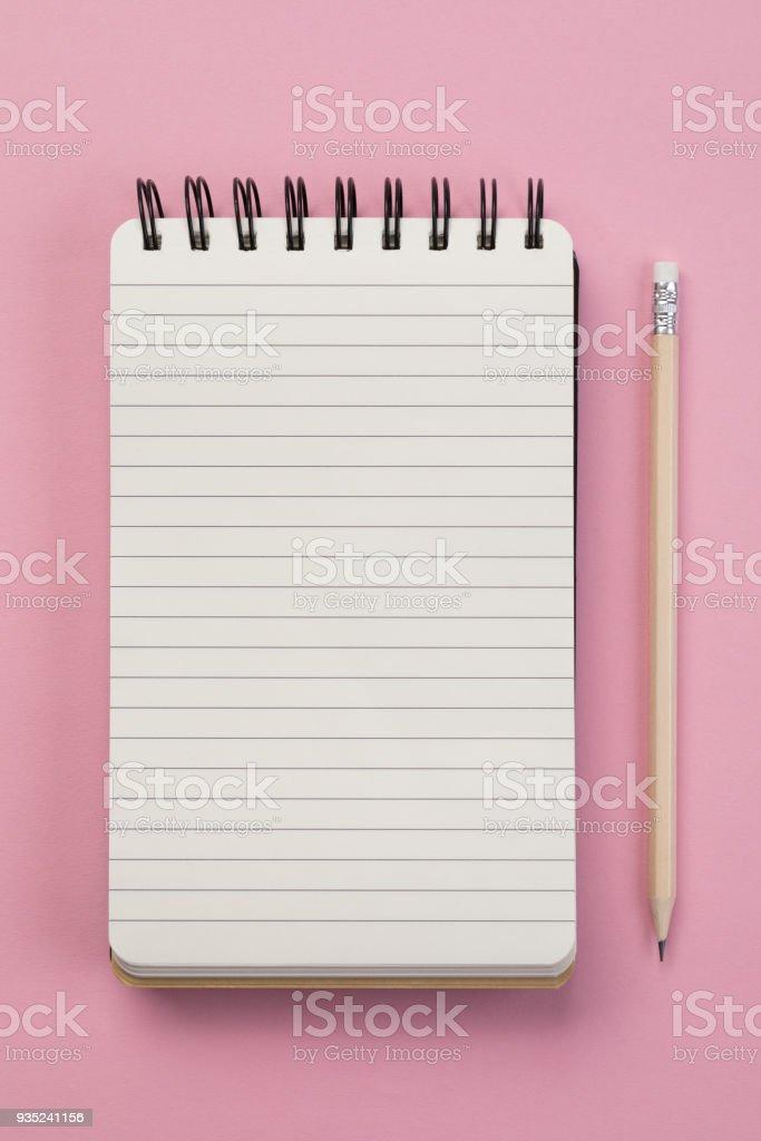 Spiral notebook on pink background