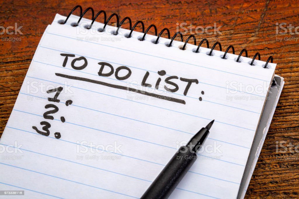 To do list - handwriting in a spiral notebooks against grunge wood