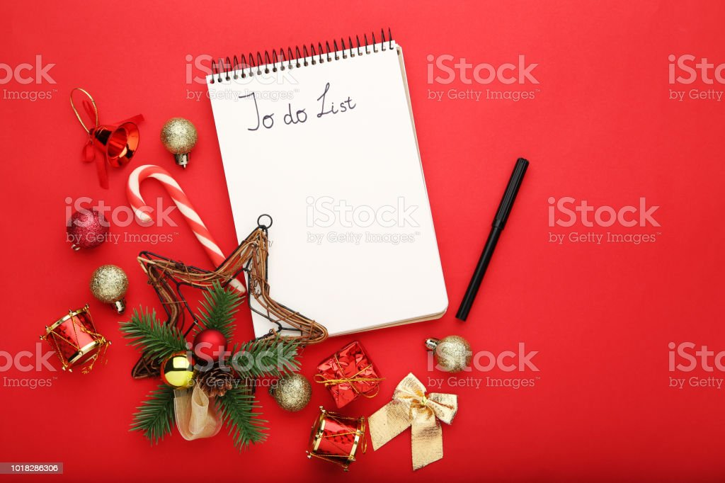 to do list in notepad with christmas decorations on red background royalty free stock photo