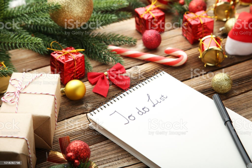 to do list in notepad with christmas decorations on wooden table royalty free stock photo