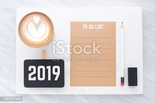 1186985932 istock photo 2019 to do list on brown recycle paper with pencil,clip blackboard,pencil,eraser and coffee cup on white and grey marble table.mock up for adding text,new year resolution concept. 1022237420