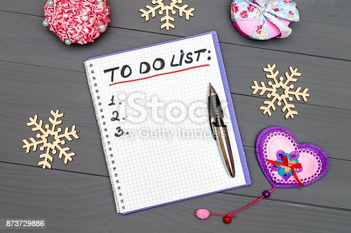 istock To do list paper page with pan and New Year ornaments on the wooden desk table surface with copy space 873729886