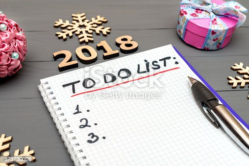 istock 2018 to do list paper page with pan and New Year ornaments on the wooden desk table surface with copy space 873730026