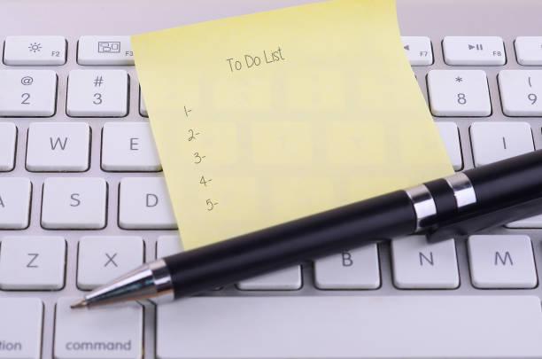 aby zrobić listę słowo na lepkie zauważyć z nowoczesną klawiaturą w tle. - post it notes zdjęcia i obrazy z banku zdjęć