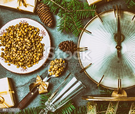 istock NEW YEARS EVE TRADITION to eat spoon of lentil at midnigth. Vintage clock, lentil amd Christmas decoration on gray background. Top view 891123272