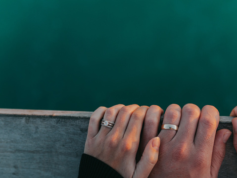A married couple hold hands on a pier railing above the beautiful Gulf of Mexico.
