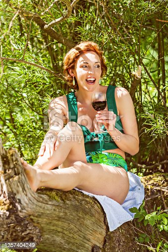 Young redheaded woman in a bikini with a glass of wine in her hand, sitting on a tree stump and having fun.