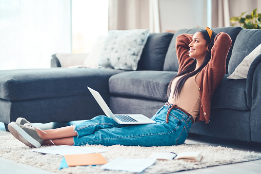 Shot of a young woman relaxing while working in the living room at home