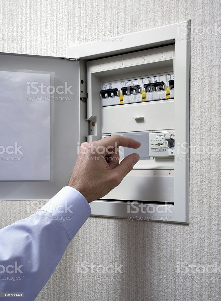 a male hand is interacting with a open fuse box.