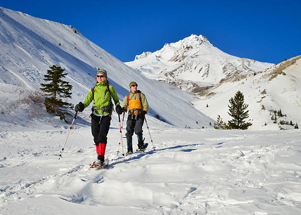 To snowshoers in the snow on a mountain stock photo