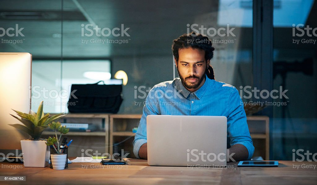 To stay productive you need to stay persistent Cropped shot of a young designer working late on a laptop in an office 20-29 Years Stock Photo