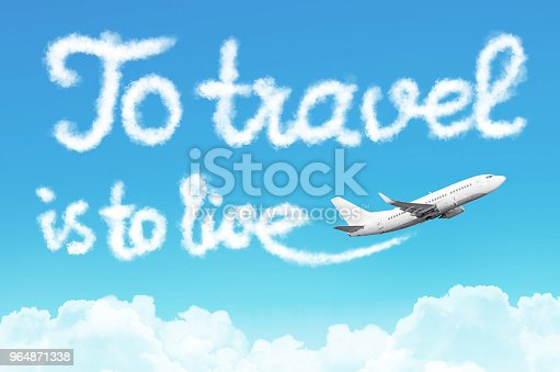 925925874 istock photo To travel is to live - phrase drawn from clouds airplane in the blue sky, concept travel tourism holiday vacation. 964871338