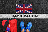 Man in shoes with bag standing next to line with word IMMIGRATION and flag of United Kingdom on asphalt road