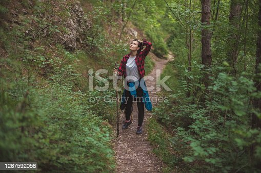 An image of a woman, during her walk throughout the forest. She's up for a long walk and she took a break to enjoy the breath-taking scene of wild nature.