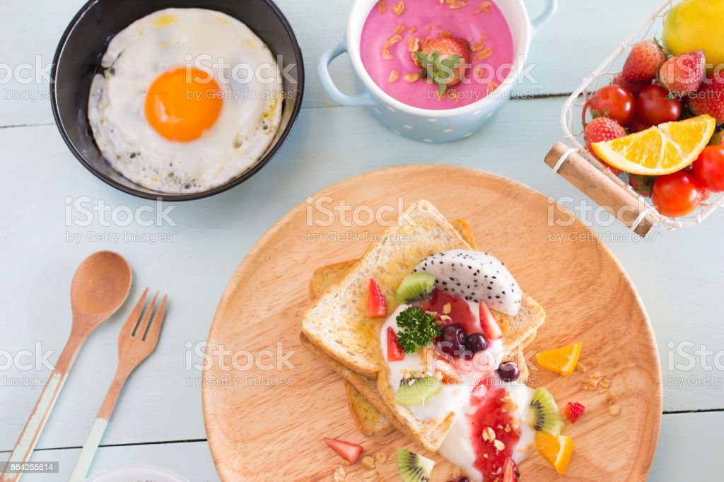 Toast and fruit total milk yogurt with fried egg in a frying pan on wood Top view. royalty-free stock photo