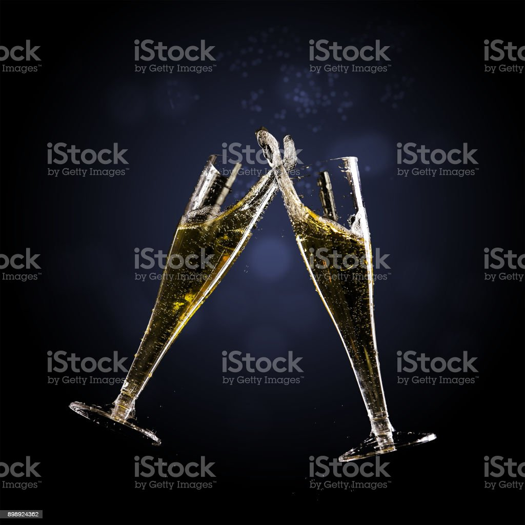 Toast champagne flutes with splash against a dark background, copy...