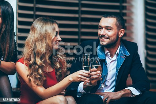 istock Toast Cheers. Beautiful young couple celebrating party event 878457860