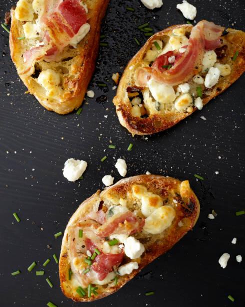 crustinis toast mit schinken, kräutern und käse - ofengemüse mit feta stock-fotos und bilder