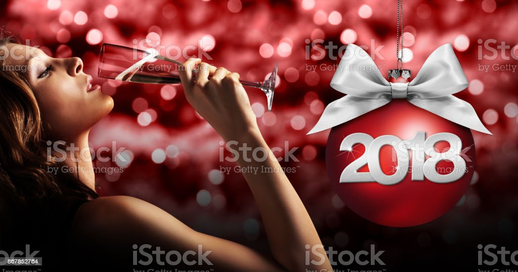 toast New Year's Eve, woman drinking sparkle wine on red blurred stock photo