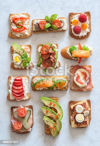 An assortment of tartines, small open-faced sandwiches with various toppings both savory and sweet.