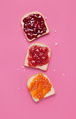 istock Toast slices with fruit jam on a pink background viewed from above. Selection of bread slices with fruit marmalade. Top view 1009431284