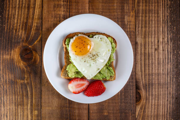 Toast with avocado and egg in heart shape Toast with avocado and egg with heart shape  on white plate breakfast stock pictures, royalty-free photos & images