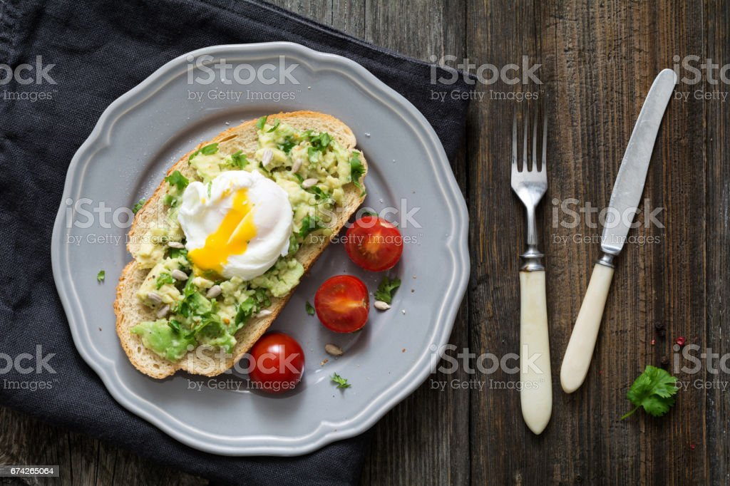 Toast with avocado and poached egg stock photo