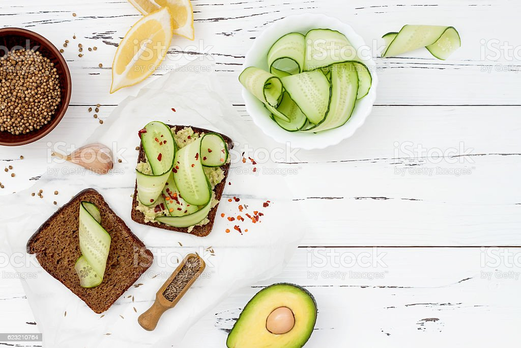 Toast with avocado guacamole and cucumber slices.  Spicy avocado sandwiches stock photo