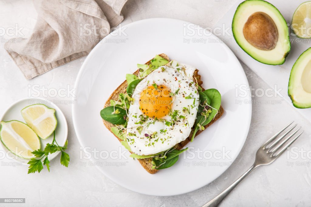 toast with avocado, spinach and fried egg stock photo