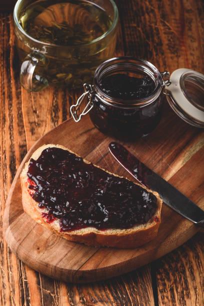 toast mit beerenmarmelade und grünem tee - ribiselmarmelade stock-fotos und bilder