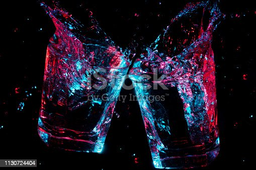 2 rocks glasses clinking a toast with colorful glowing liquid splashing from them on a black background