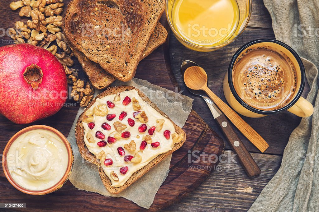 Toast with hummus, wallnuts and pomegranate bildbanksfoto