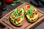Vegan or Vegetarian Toast with mashed avocado, arugula served on wooden board