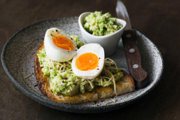 toast mit zerdrückte avocado, ei und käse auf dunklem hintergrund - zimt gurken stock-fotos und bilder
