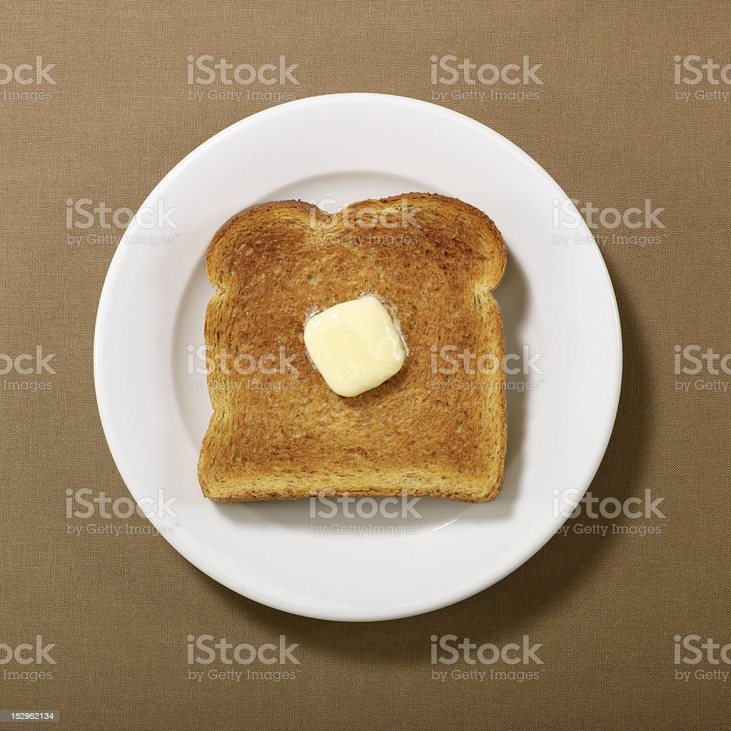 Toast with melting butter on round plate stock photo