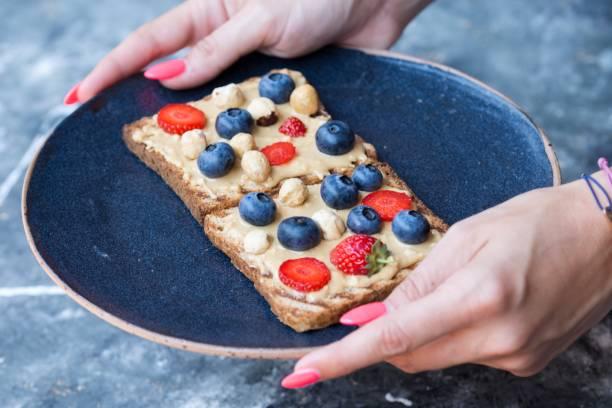 toast mit erdnussbutter und beeren und erdnüssen auf handgemachte keramik-platte - zuckerfreie lebensmittel stock-fotos und bilder