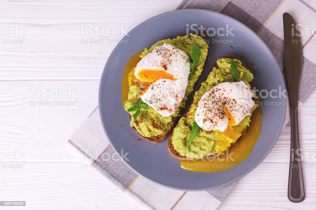 Toast with poached egg, puree avocado, spices and arugula stock photo