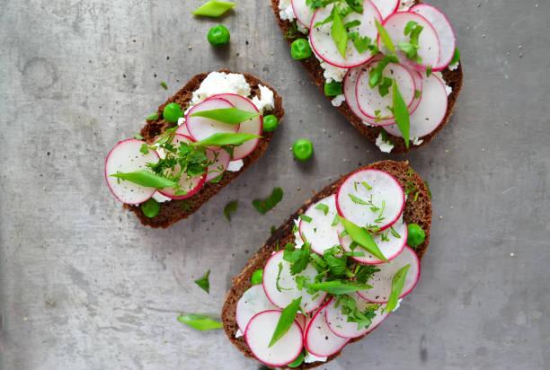 toast mit ricotta, radieschen und grünen erbsen - radieschen salat stock-fotos und bilder