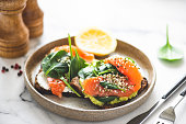 Toast with salmon, mashed avocado and baby spinach. Healthy appetizer, breakfast, lunch or snack