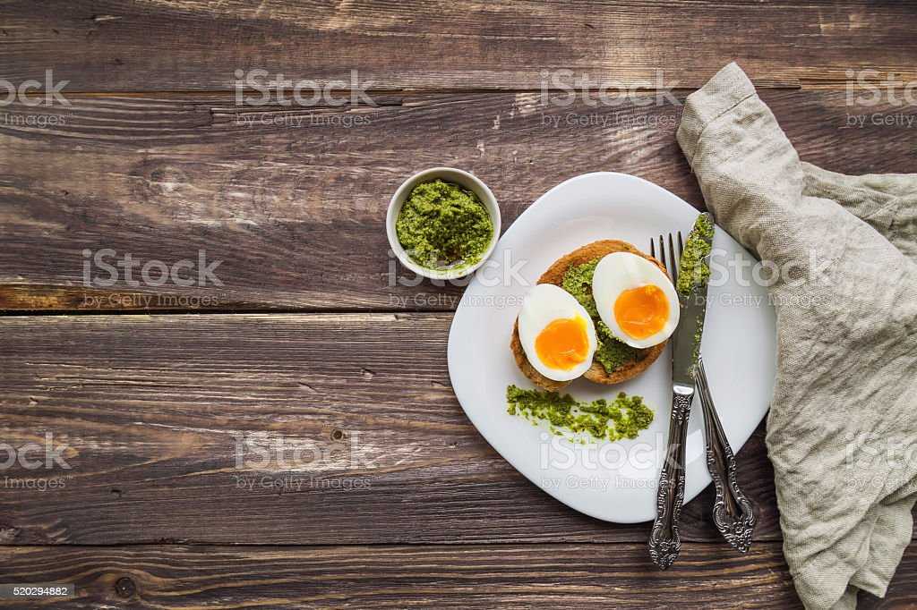 Toast with soft-boiled egg and pesto sauce stock photo