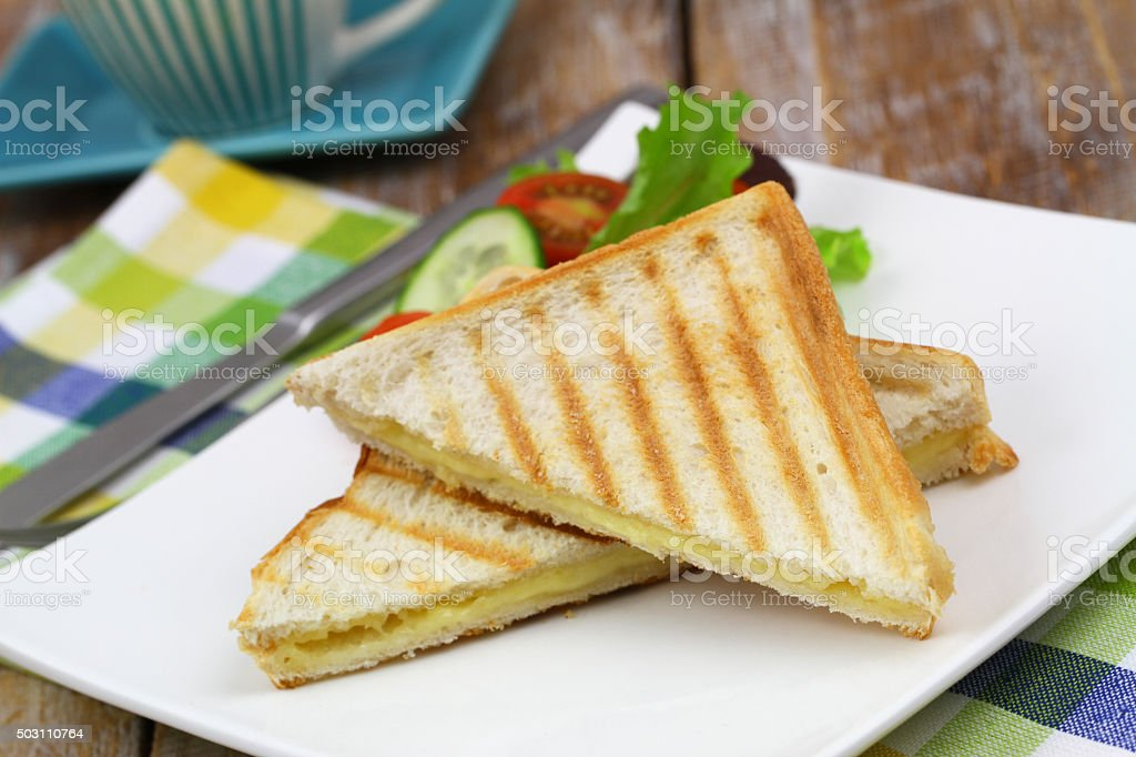 Toasted bread with melted cheese and green side salad stock photo
