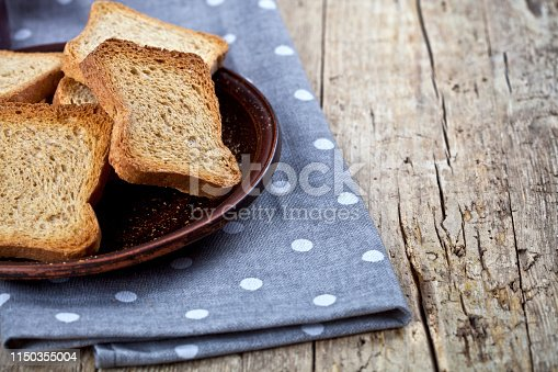 Toasted cereal bread slices on brown ceramic plate closeup on linen napkin on rustic wooden table background. Healthy food for breakfast with copy space.