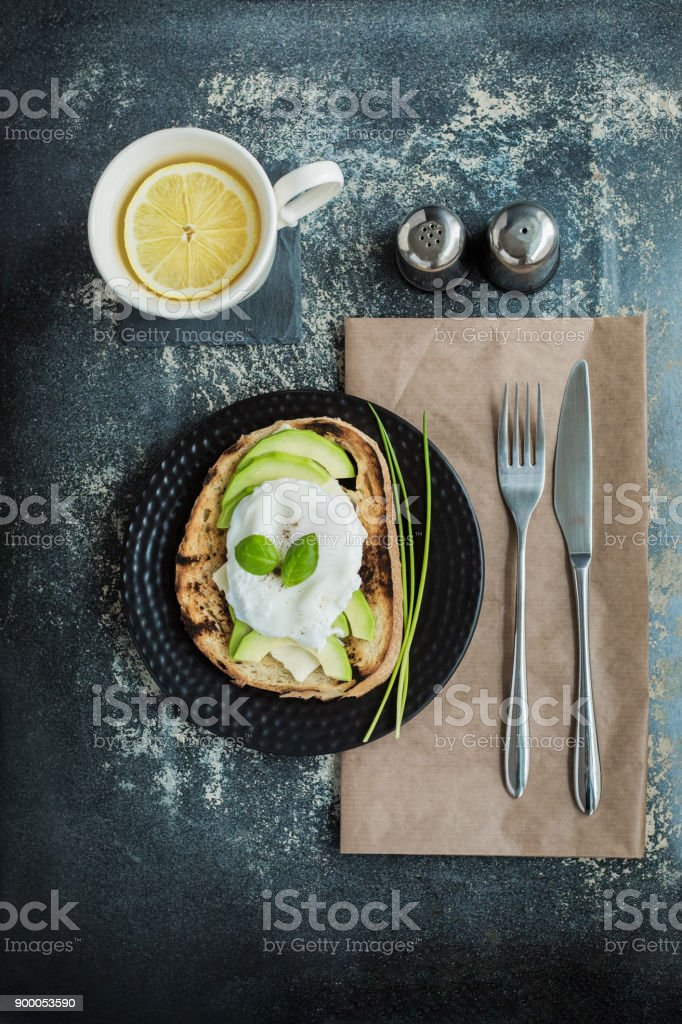 Toasted slice of rustic bread topped with sliced avocado and pouched egg on dark background stock photo