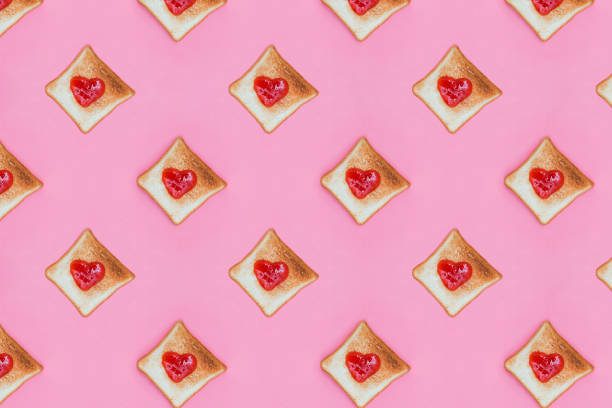 Toasted slices of bread with heart shaped jelly on top. stock photo