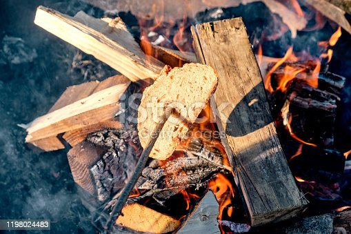 istock Toasting a piece of bread above a bonfire 1198024483