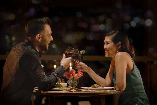 toasting couple - dinner date stock photos and pictures