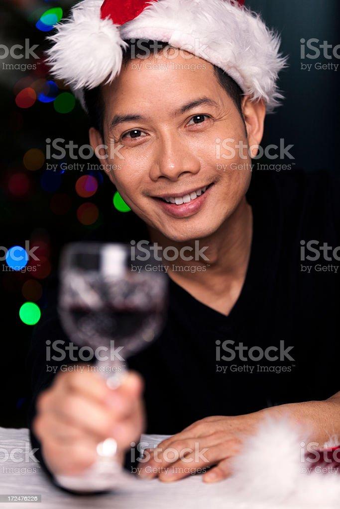 Toasting ethnic man with santa hat stock photo