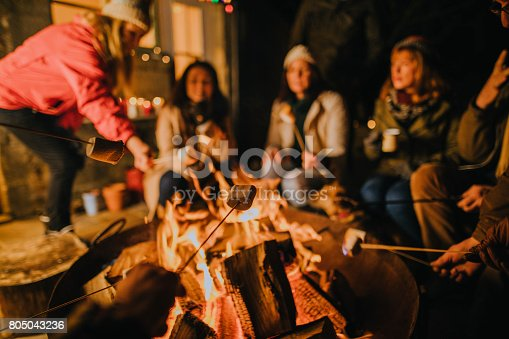 Group of mature female friends in their 30s and 40s gathered around a fire pit in a British garden.