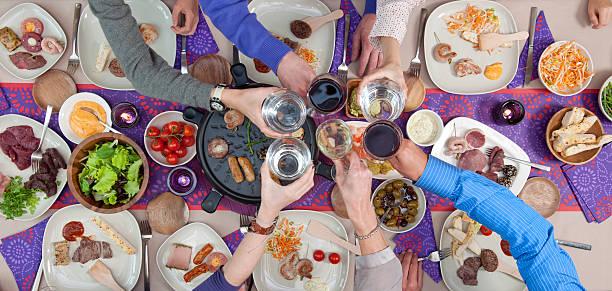 anstoßen auf esstisch mit gegrilltem fleisch und meeresfrüchte - käse wurst salat stock-fotos und bilder